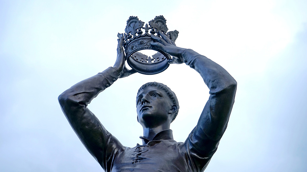 Bronze statue of a man holding a crown