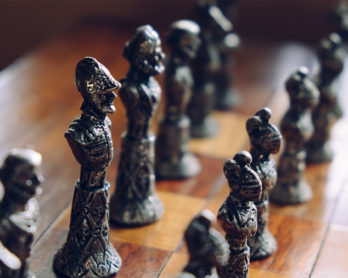 Antique chess pieces on a wooden board