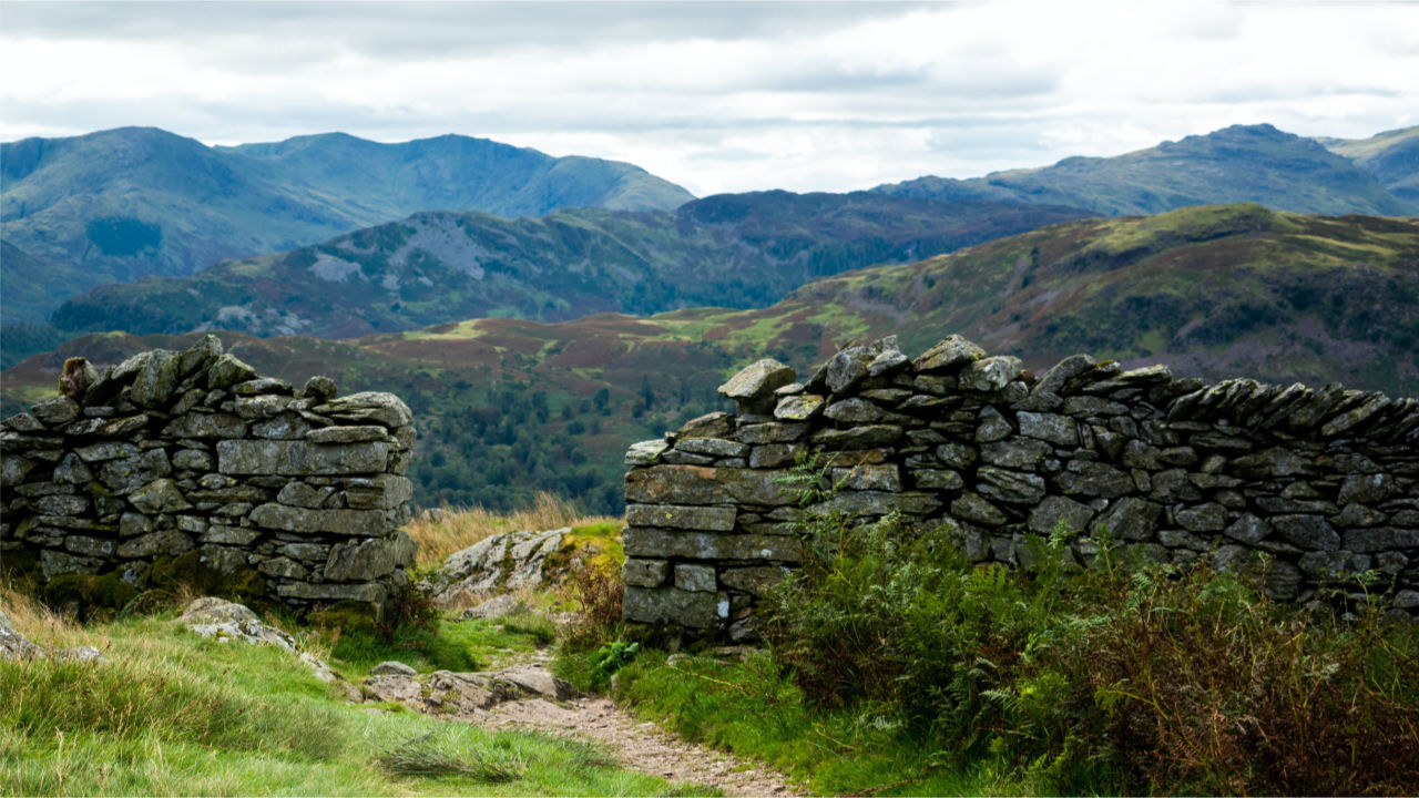 Sky, mountains, and a pathway leading through a stone wall