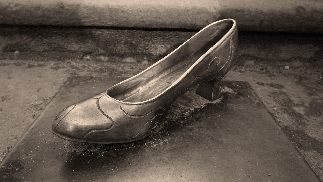 A metal sculpture of a woman's dress shoe.