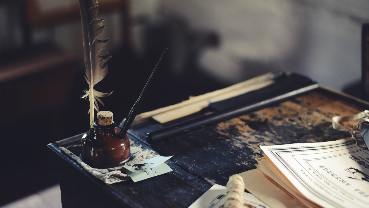 A feather quill in a well of ink