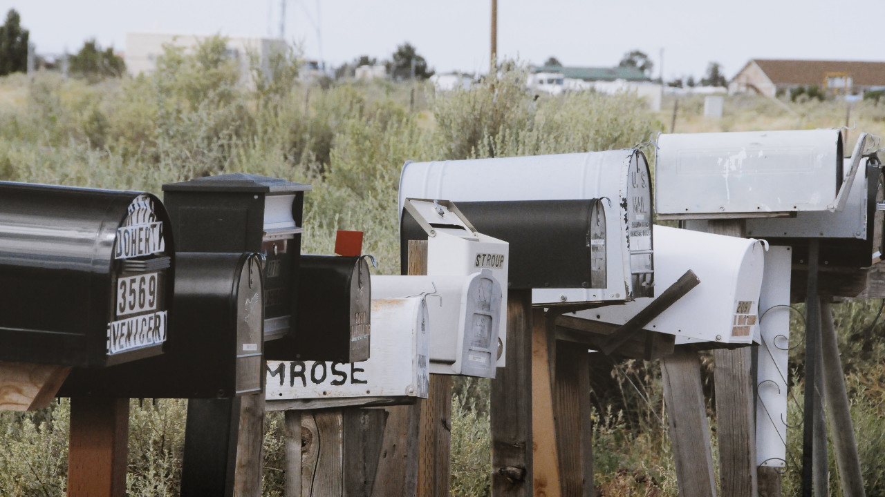 A row of mailboxes of various heights