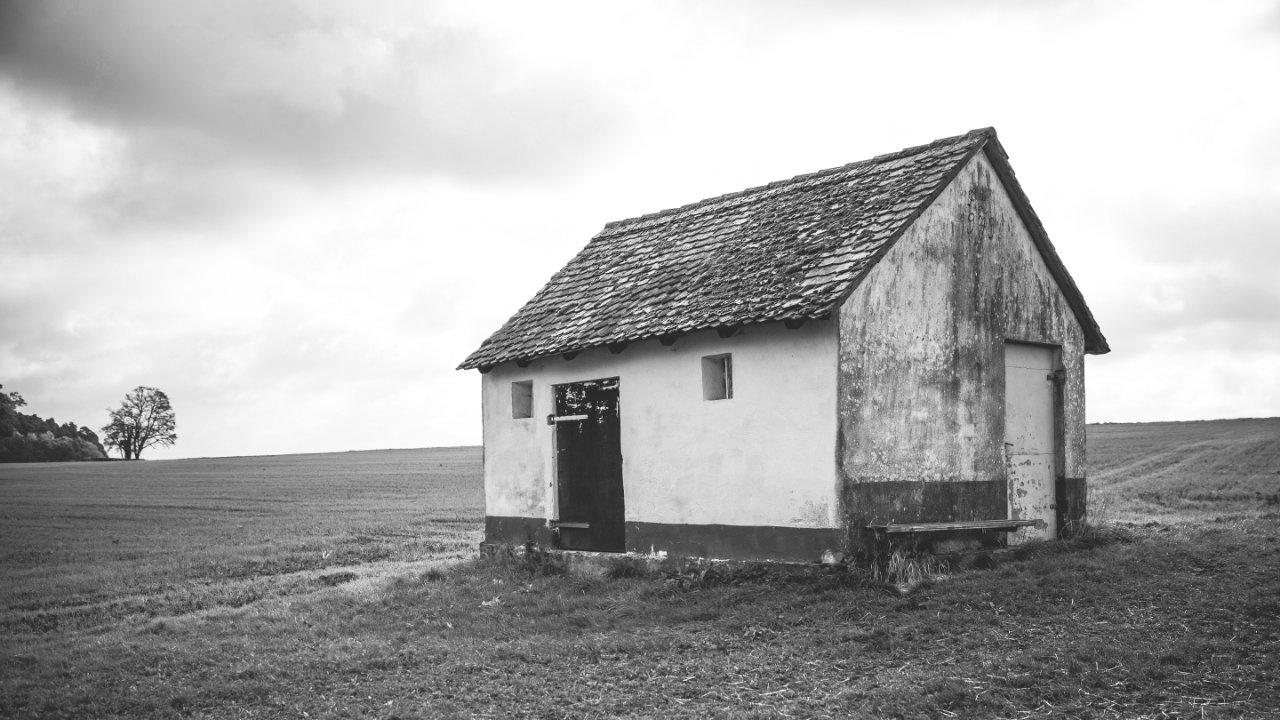 An old house on a grassy plain.